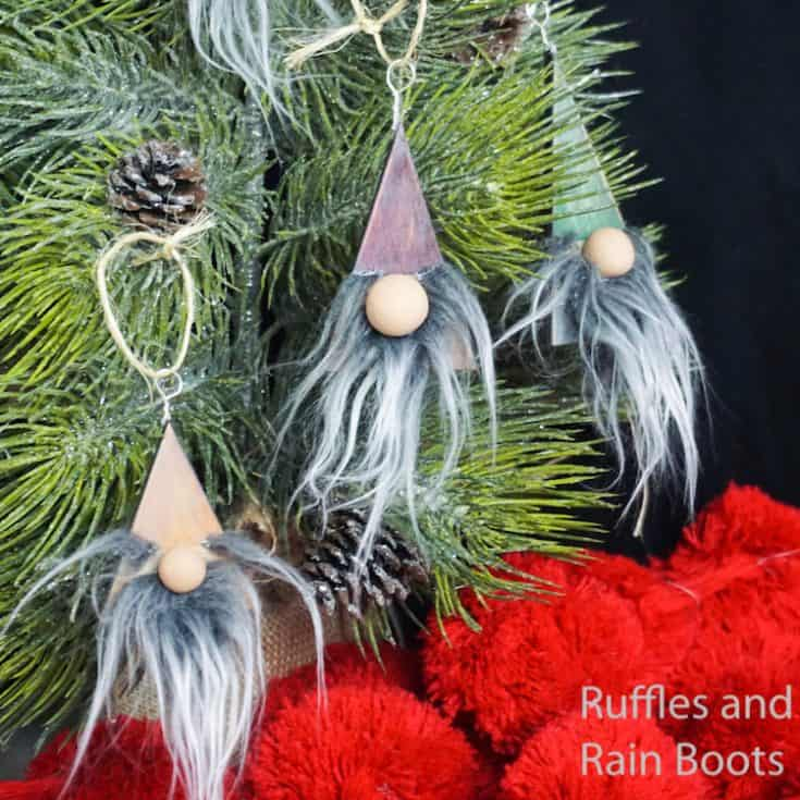 easy wood ornament gnomes hanging on a christmas tree in front of a black background