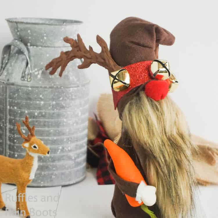 how to make a reindeer gnome with antlers on a white table with a tiny reindeer following it and a silver milk jug in the background