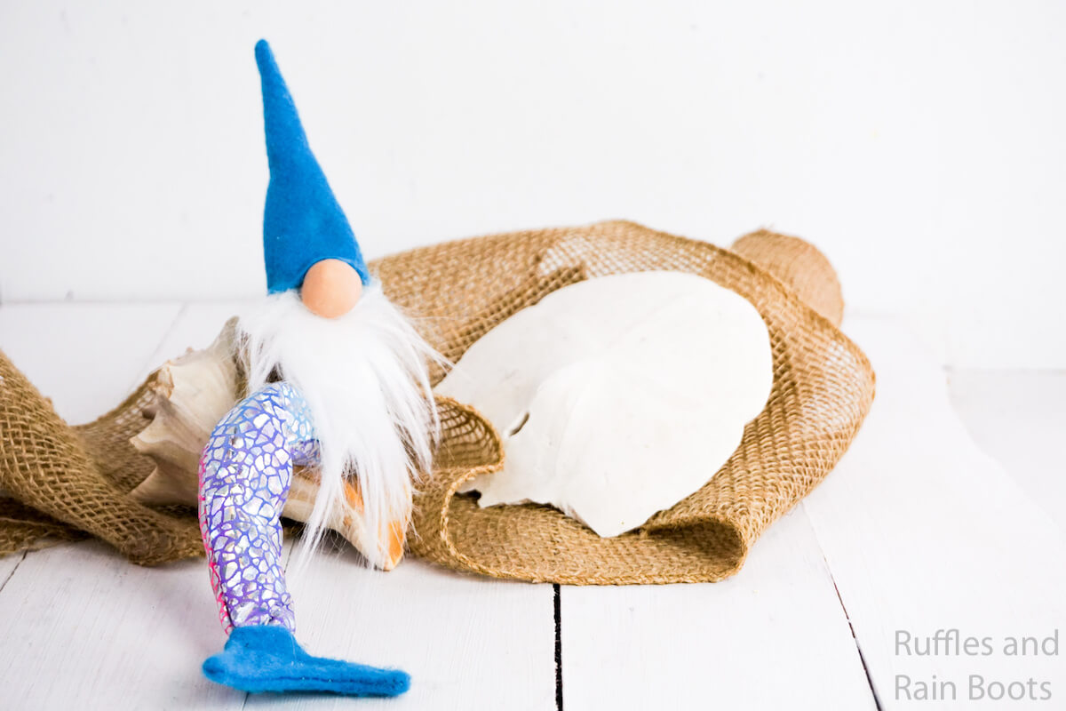 how to make a tomte mermaid on a white wood table with scattered shells