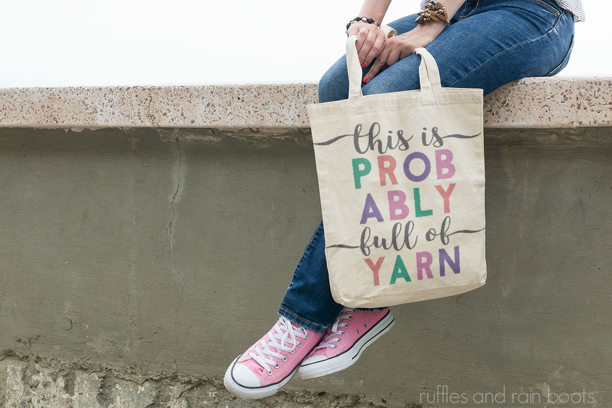 Adorable Cricut Knitting SVG tote bag held by a lady sitting on a low wall