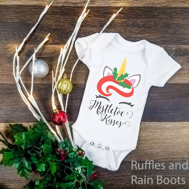 mistletoe kisses unicorn christmas svg on onesie on a dark wood background with a holiday swag