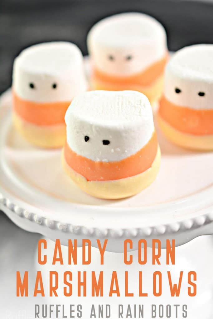Adorable Halloween Dipped Marshmallows Party Food on a cupcake platter on a black background with text which reads candy corn marshmallows