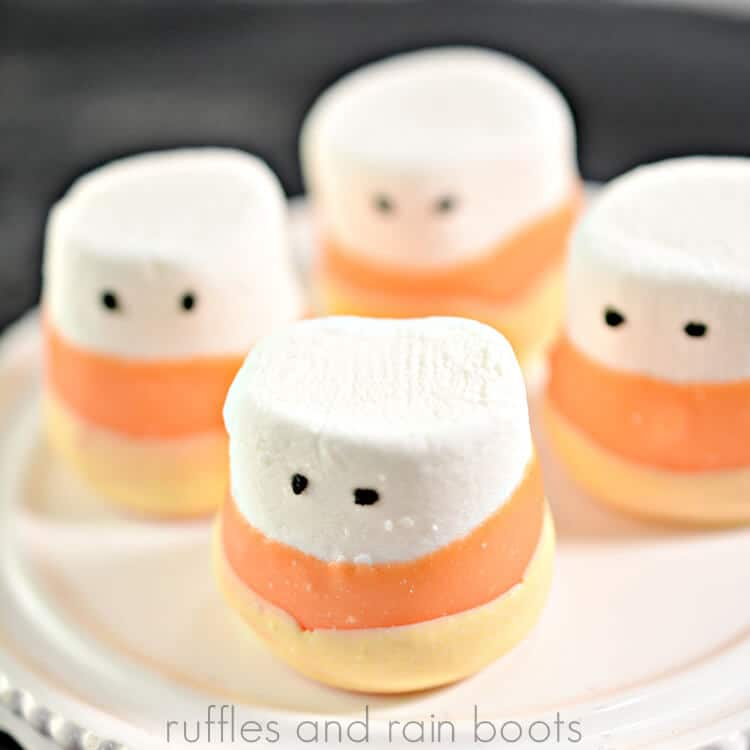 cute candy corn dipped marshmallows on a cupcake platter