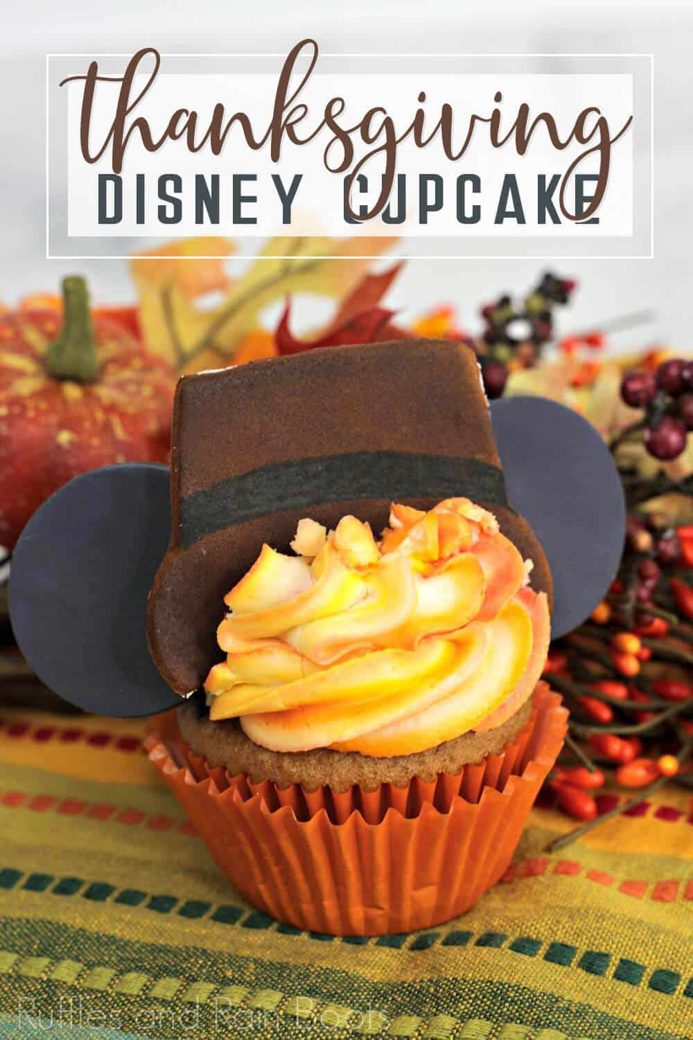 Spiced cake cupcake decorated like Mickey mouse pilgrim for Thanksgiving on napkin with fall pumpkin