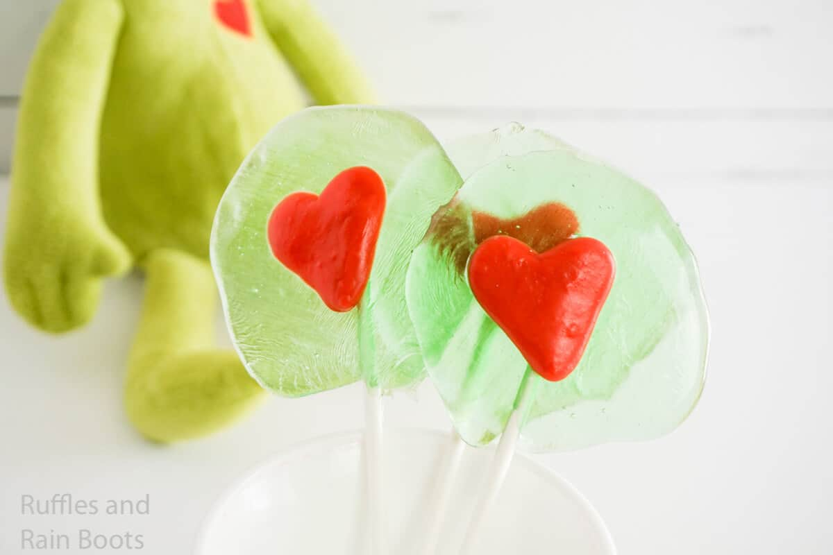 how to make grinch lollipops with a candy heart on a white wood background