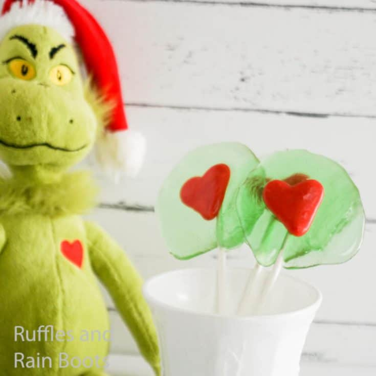 how to make homemade lollipops that are grinch themed on a white wood background with a grinch toy