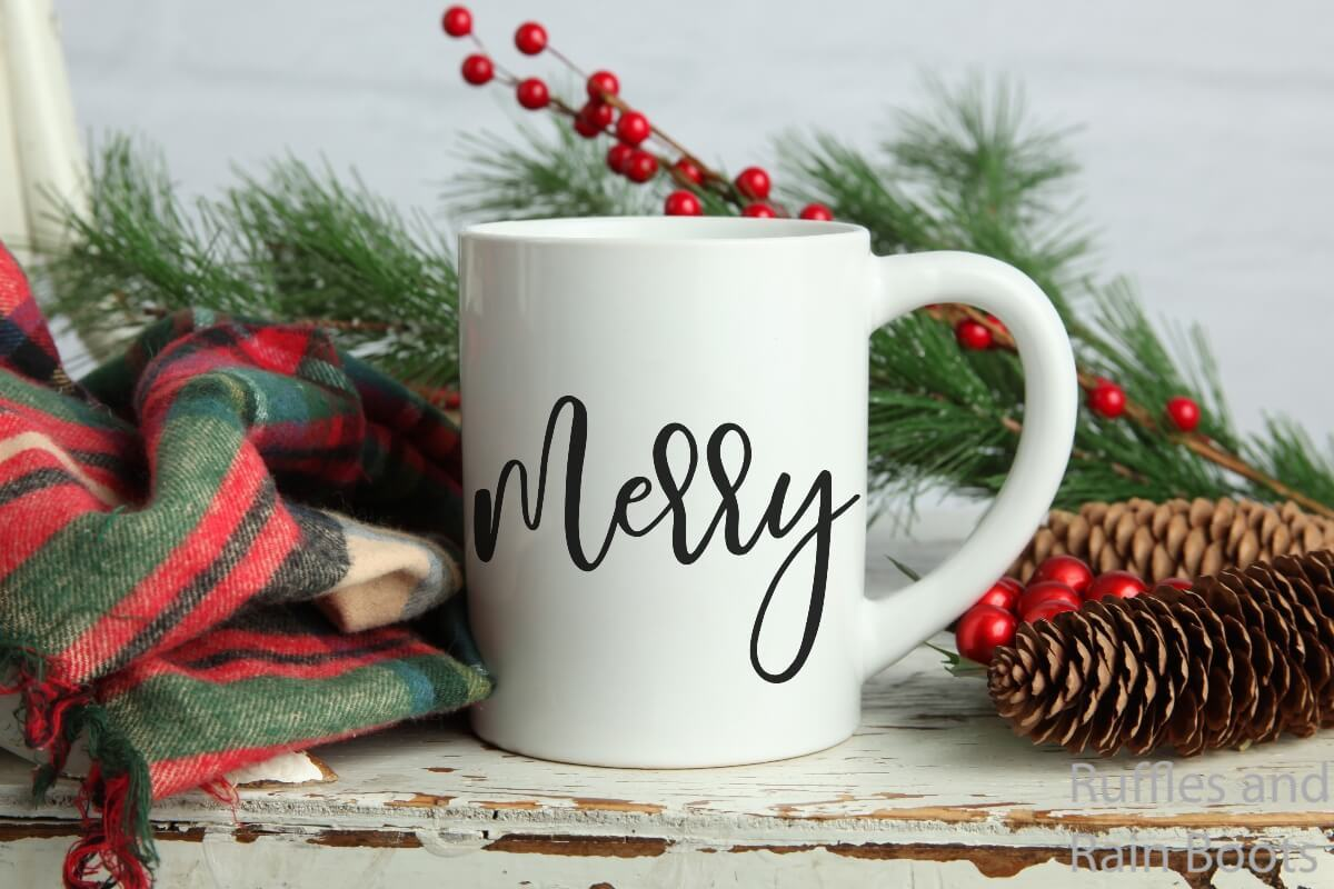 script merry christmas cut file for Cricut or Silhouette on a mug on a wood table with various holiday decor scattered around