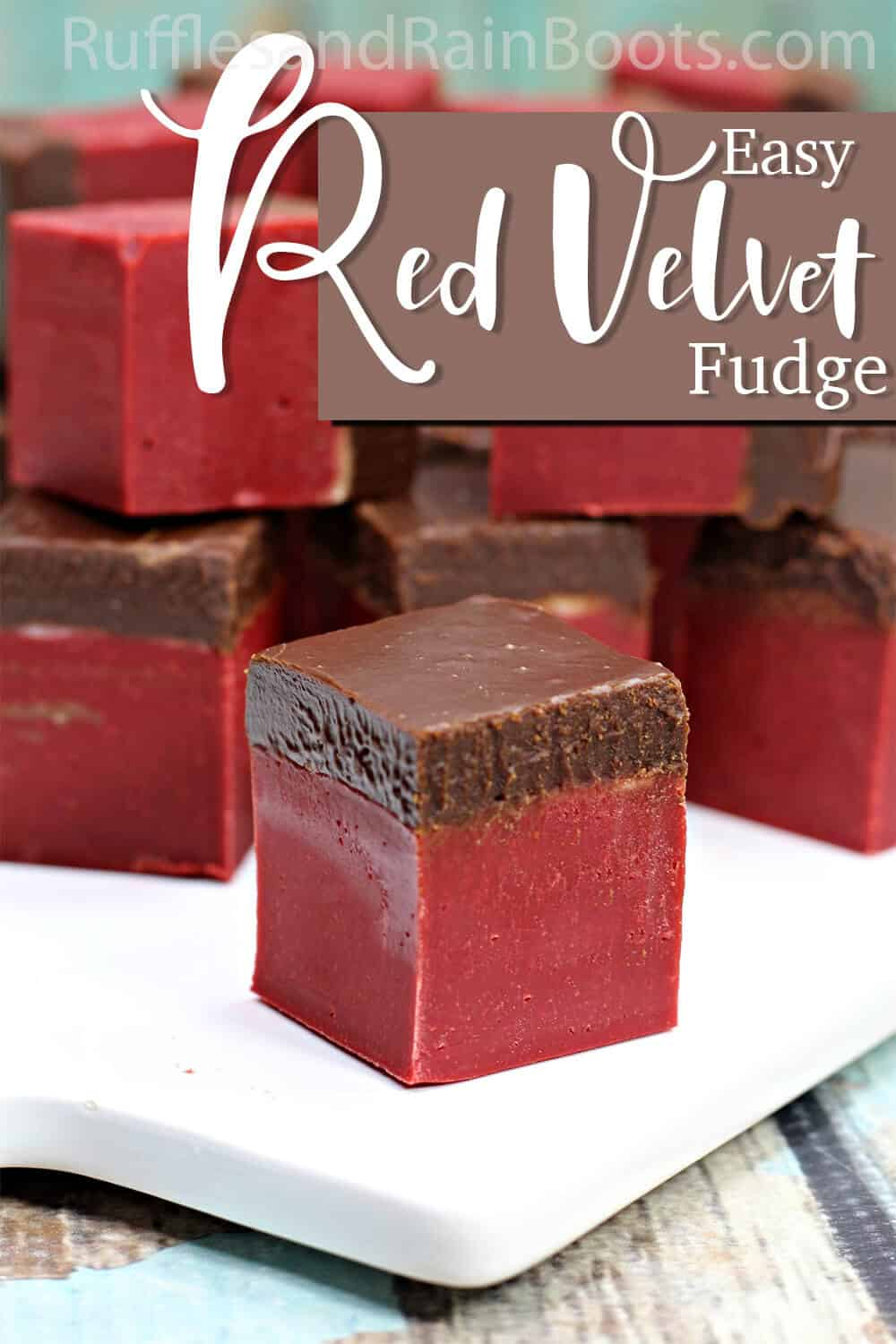 single red velvet and dark chocolate fudge on a white plate with text which reads easy red velvet fudge recipe