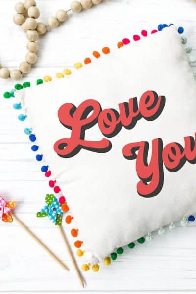 Love You SVG on a rainbow pom pom pillow