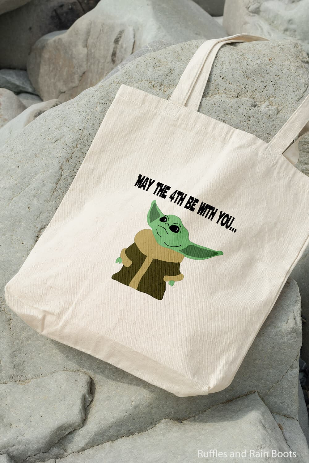 baby yoda svg file for cricut or silhouette on a canvas bag on rocks