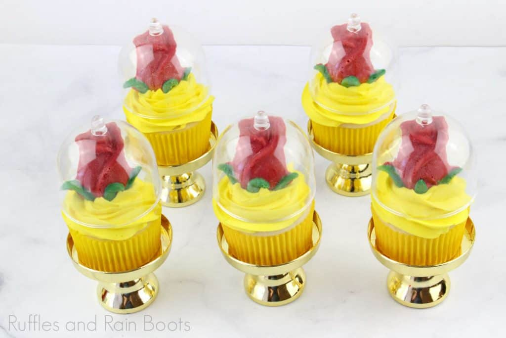 5 Princess Belle cupcakes on the cupcake stands with a white background