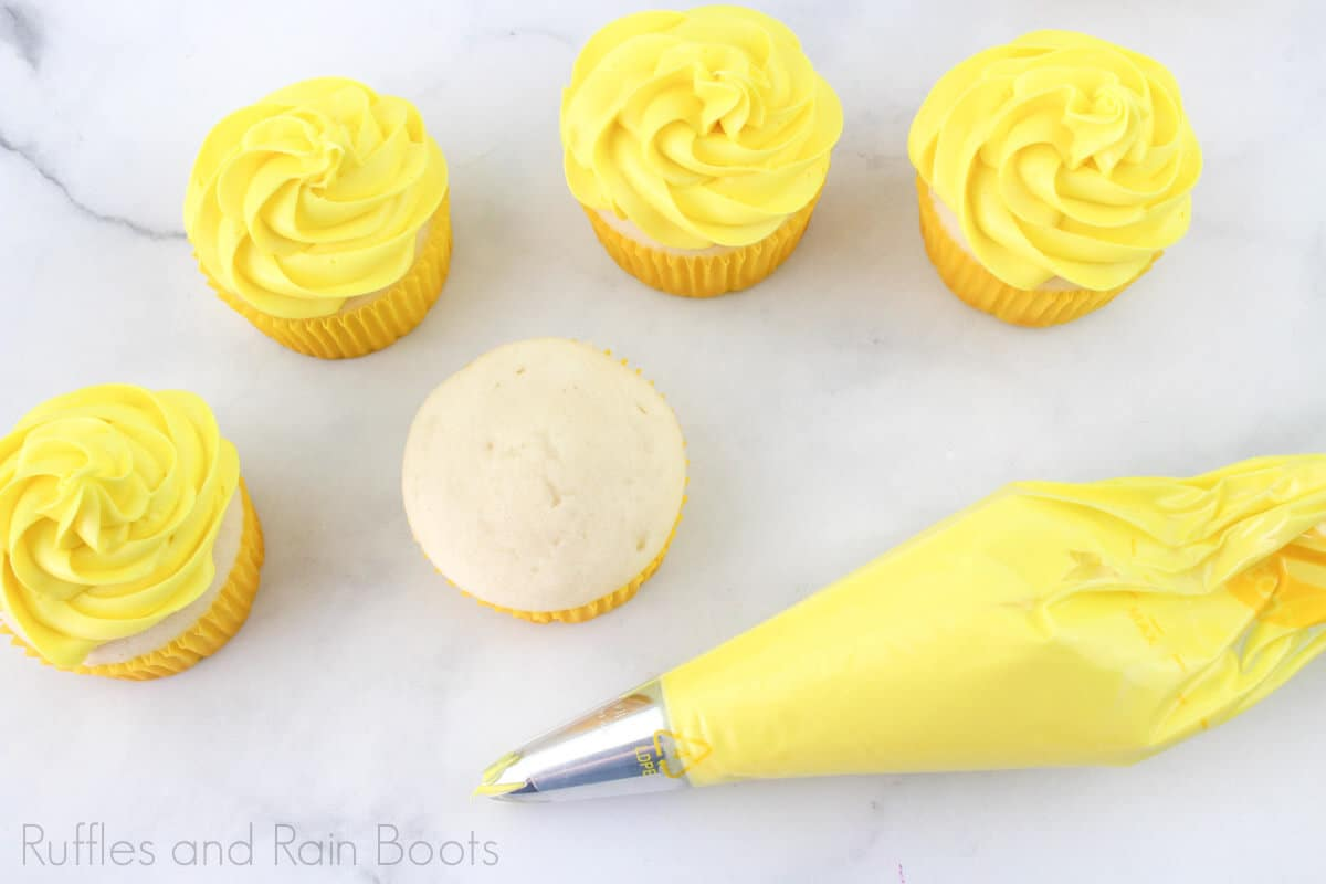 process photo of piping yellow frosting onto the princess belle cupcakes on a white background