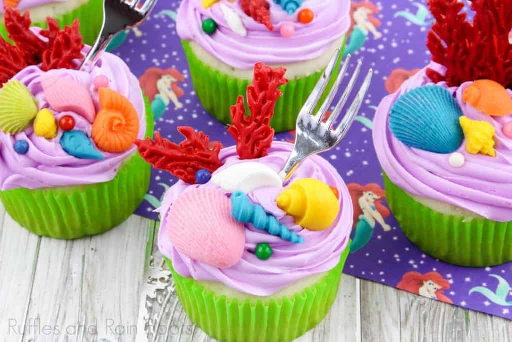 horizontal image of princess ariel cupcakes on a wood background