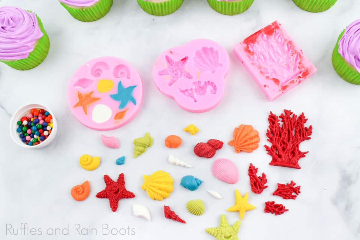 horizontal image of the sea decor molds and finished elements for the dinglehopper cupcakes on a white background