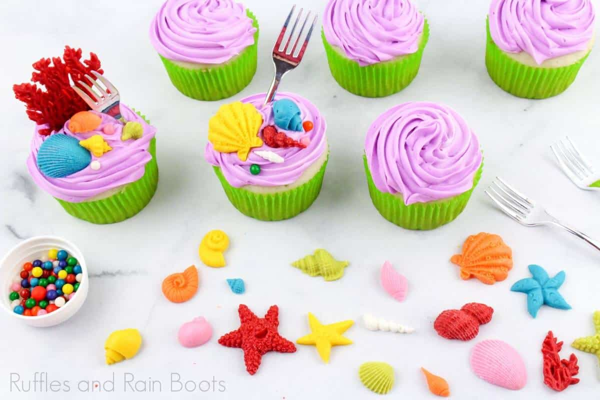 horizontal image of paritally finished princess ariel cupcakes with the sea frosting decor next to them on a white background