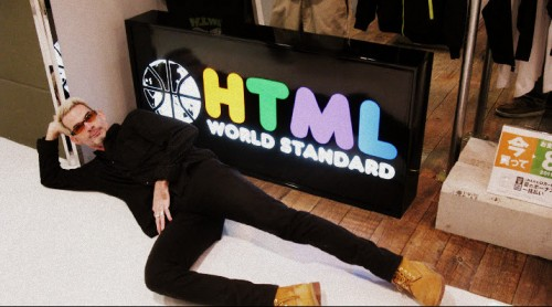 Mike Smith lying in front of a shop sign 'HTML World Standard'