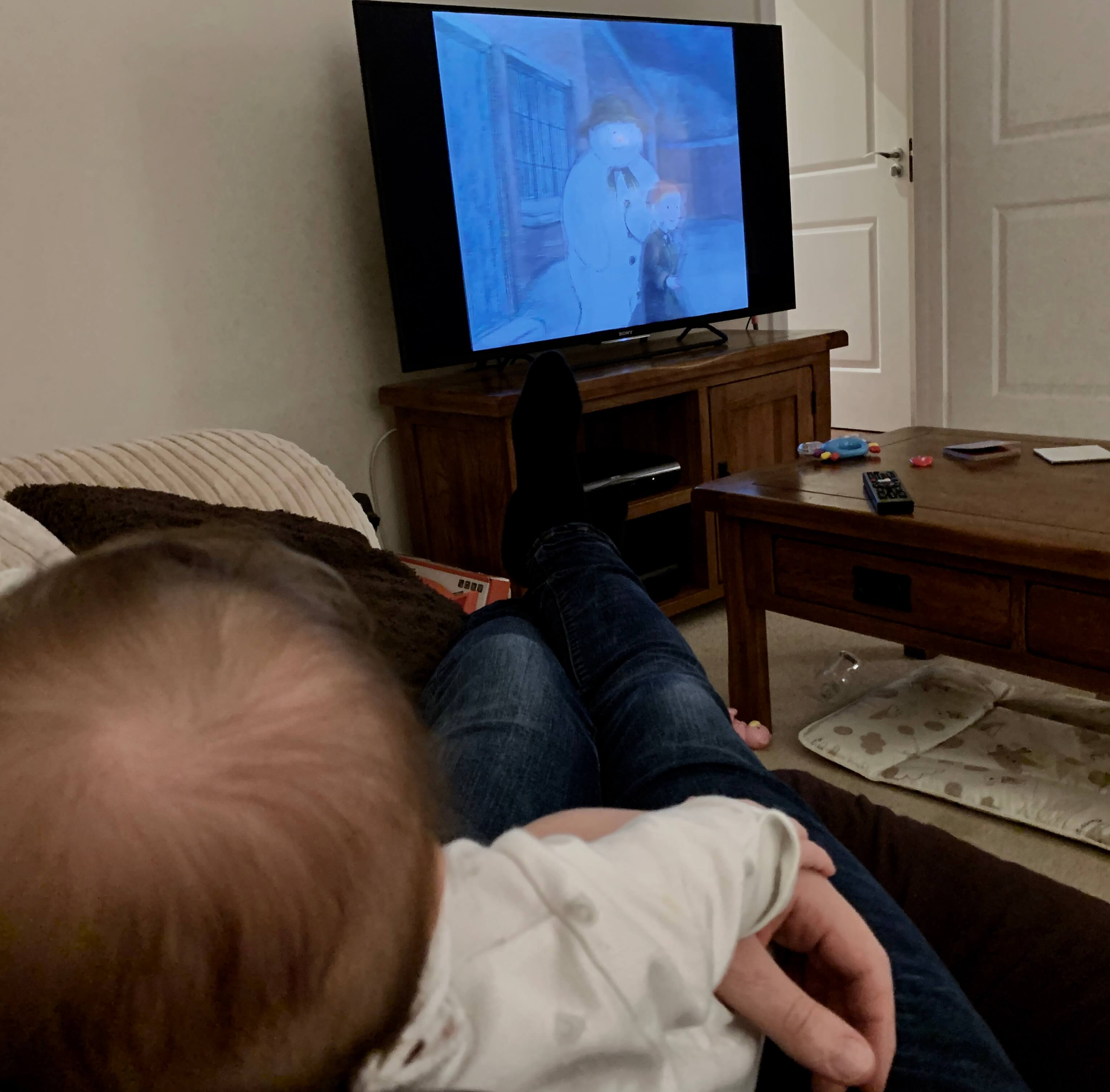 A baby in the foreground watches The Snowman in the background