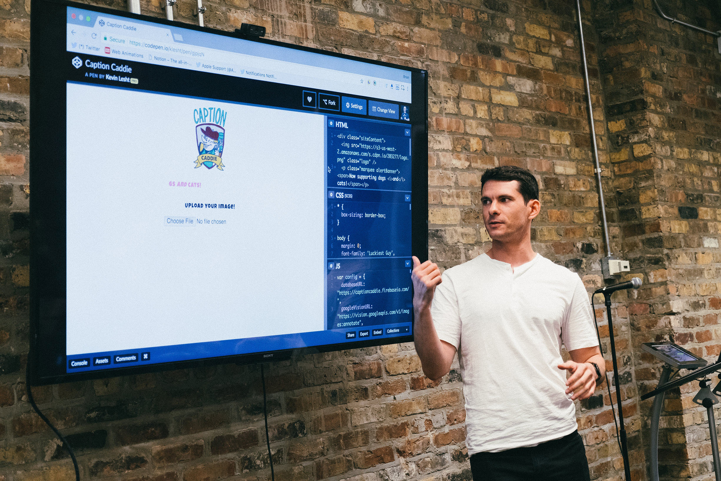 Kevin pointing to a large television of the CodePen he made, Caption Caddie