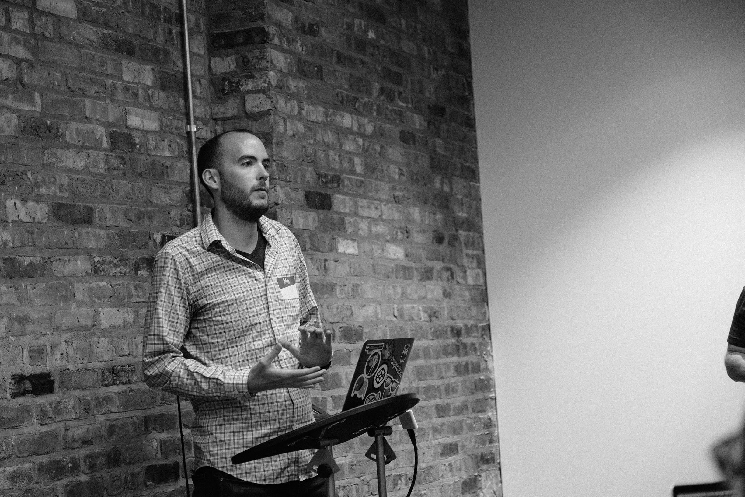 Austin presenting in front of brick wall