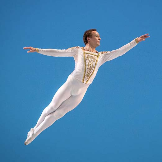 A danseur in brisé (a leap with the legs together) on a blue background
