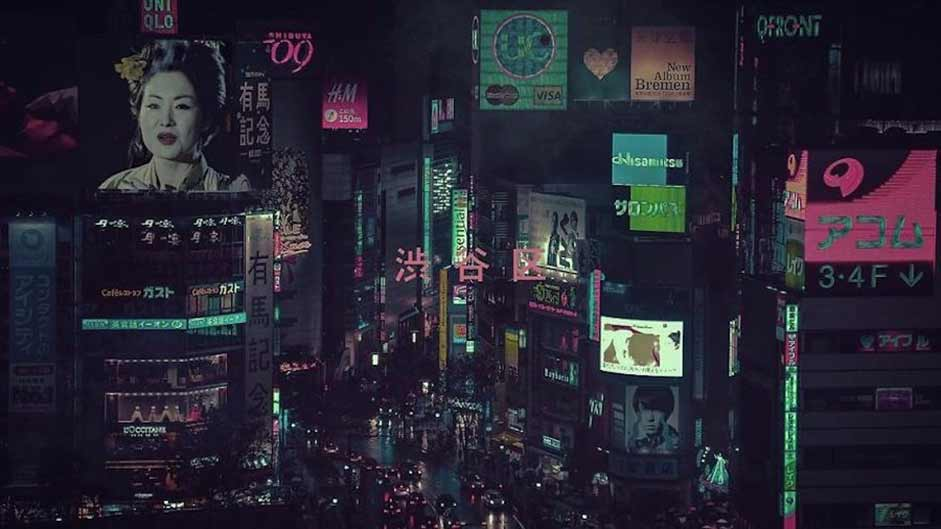 A view of video billboards at night in a Japanese shopping district