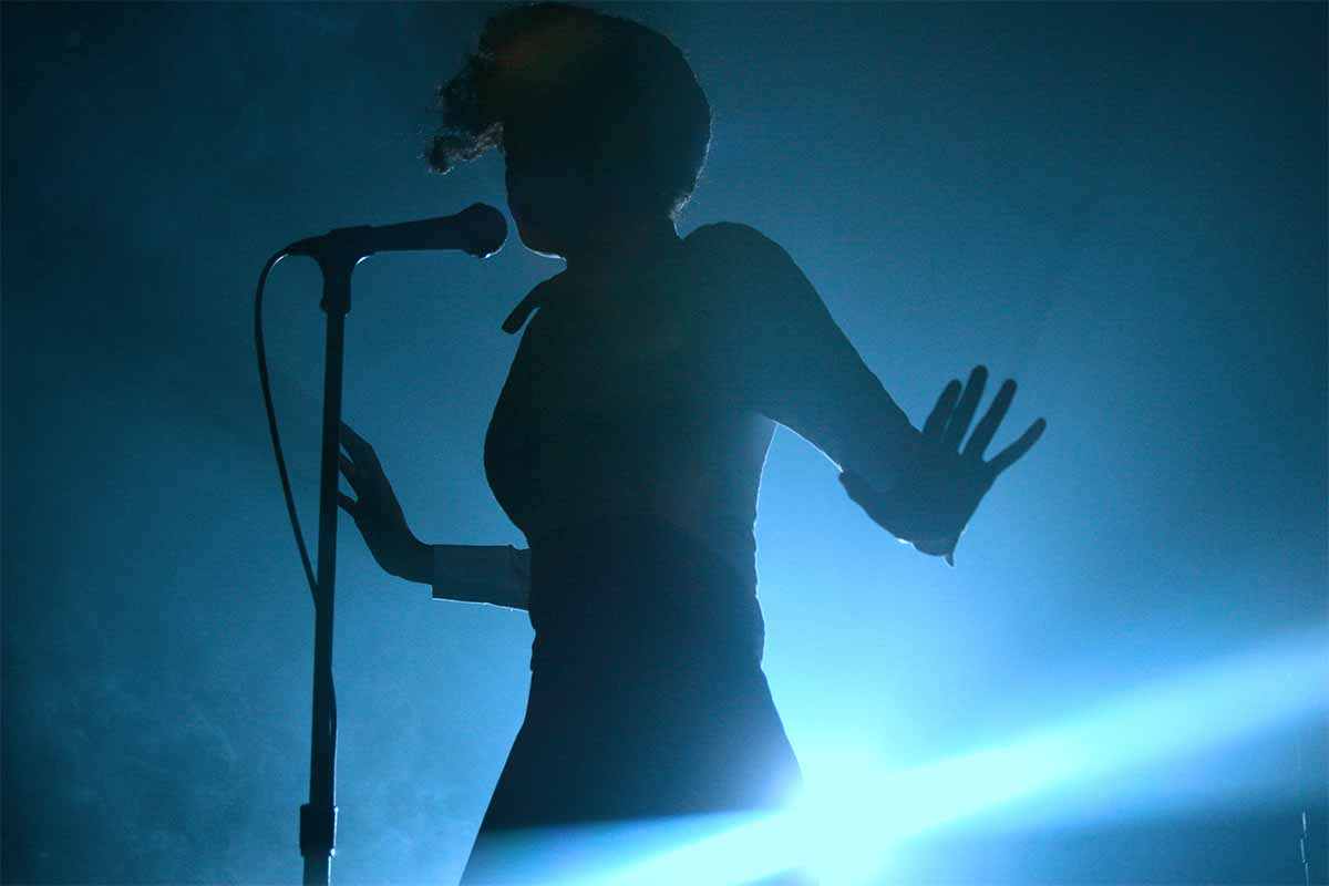 Photograph of Janelle Monae in concert, shot in sillouette against a blue light