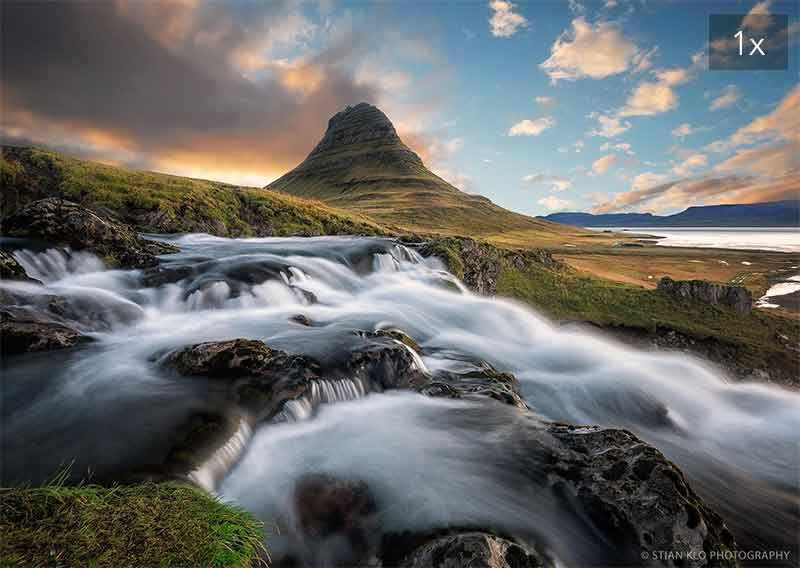 Photograph of a blurred waterfall in Iceland with a conical mountain behind it