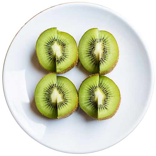 A photograph of sliced kiwifruit on a while plate