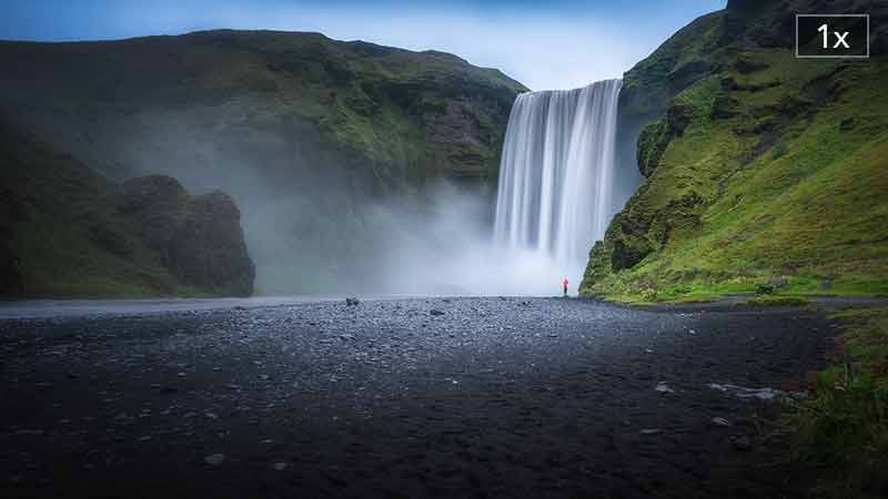 Photograph of a tiny human figure in a red rainjacket drawfed by the scale of the Skógafoss waterfall in Iceland