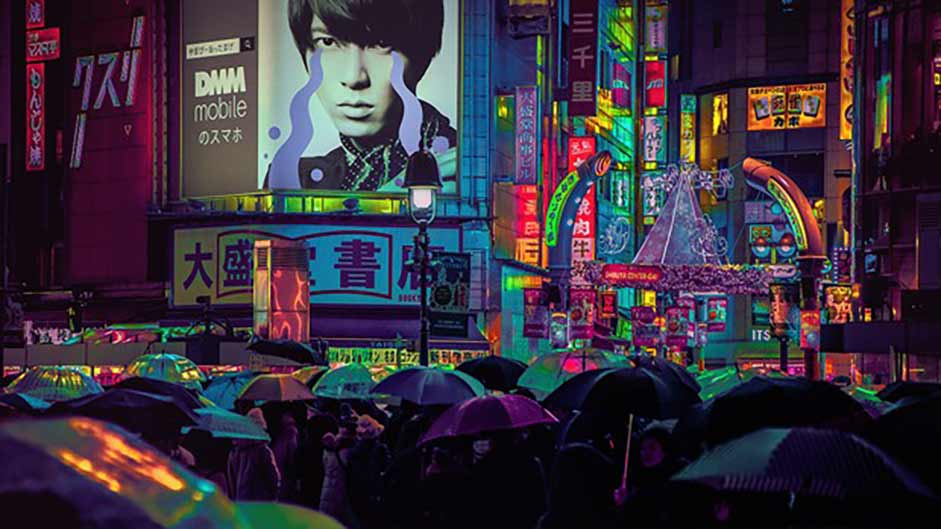 A view of video billboards at night in a Japanese shopping district, with pedestrians below