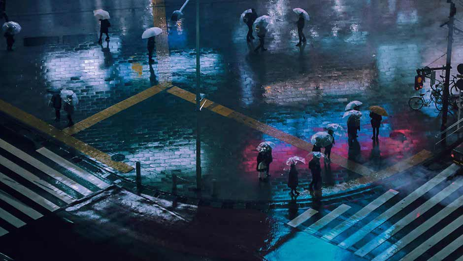 Pedestrians crossing a rain-slick street intersection at night, covered by umbrellas