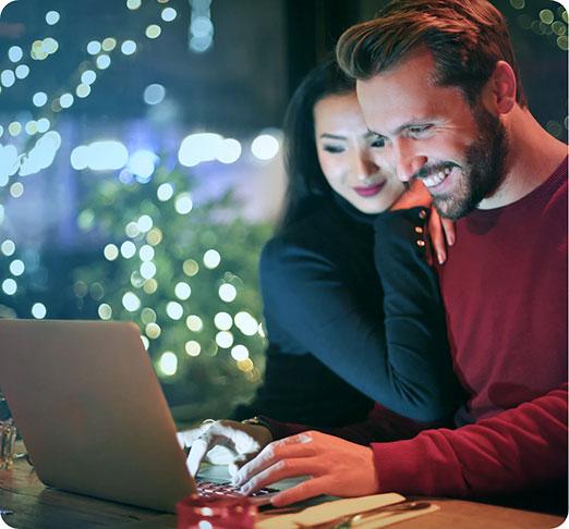 Man and woman smiling at a computer