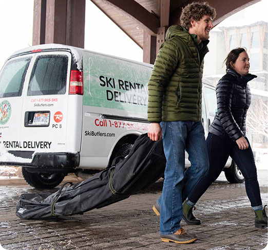 Man and woman walking with ski bags