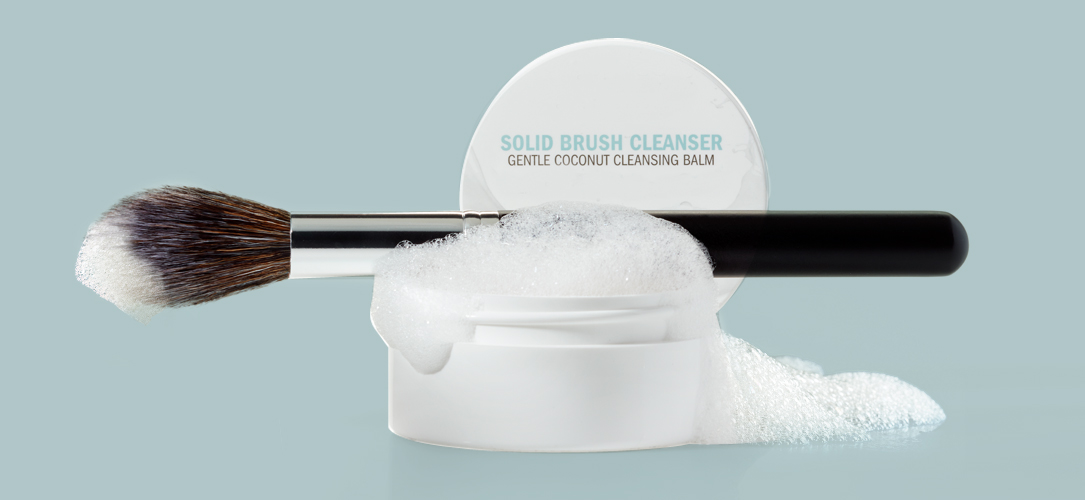Japonesque Solid Brush Cleanser in the gentle coconut cleansing balm open and filled with soap suds and with a clean makeup brush with suds on it because the solid cleansing balm is perfect for cleaning brushes and maintaining their quality.