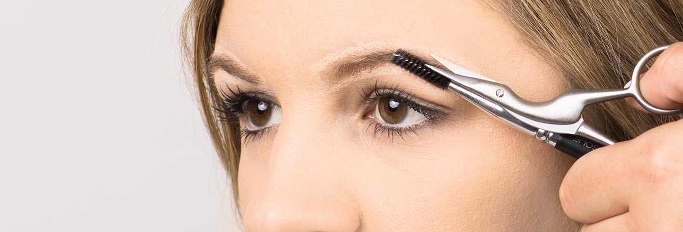 Using the JAPONESQUE Pro Performance Brow Spoolie, brush brows upwards and trim straggly brow hairs with the Pro Performance Stork Scissor.