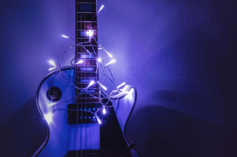 guitar and string lights - 8 Christmas Songs That Rock KRXQ