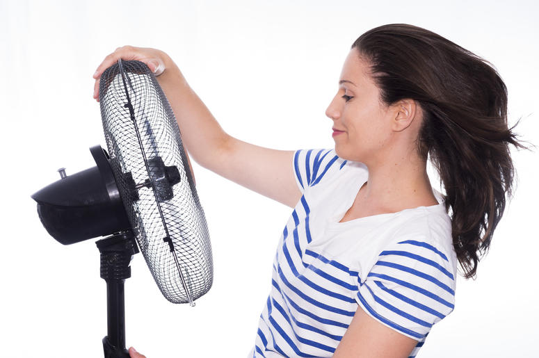 Woman cooling off with a fan