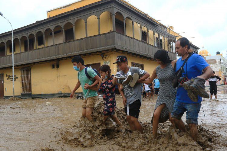 Los habitantes de la localidad vadearán por el agua mientras una inundación repentina golpea la ciudad de Trujillo, a 570 kilómetros al norte de Lima. AFP