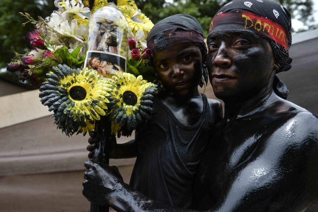 Padre e hijo se llenaron el cuerpo de aceite negro para pagar sus promesas a Santo Domingo. LA PRENSA / Jader Flores.
