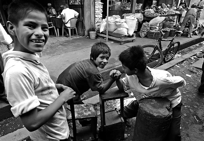 Dos niños juegan a la tercia o al pulso en el mercado de Nueva Guinea, mientras un tercero sonríe para la cámara. Uno de ellos es un joven lustrador de zapatos. La Unicef dice que en Nicaragua hay 2.4 millones de niños. De estos, según las últimas cifras oficiales disponibles —las del 2012—, unos 400 mil niños trabajan. FOTO: ÓSCAR NAVARRETE / LAPRENSA