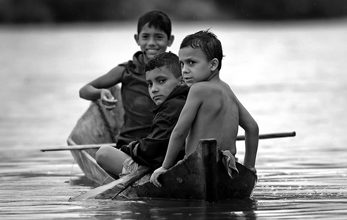 Tres niños que no superan los 10 años de edad cumplen su faena del día: pescar sin equipos adecuados en el río. La imagen fue tomada en Boca de Sábalos, Río San Juan, al sur de Nicaragua. La expresión del menor que viaja en el centro de la panga podría ser la misma que la de un pescador viejo que regresa a su casa tras una fatigada jornada. El niño que va al final, por su parte, enseña los dientes con su sonrisa. FOTO: ÓSCAR NAVARRETE / LAPRENSA