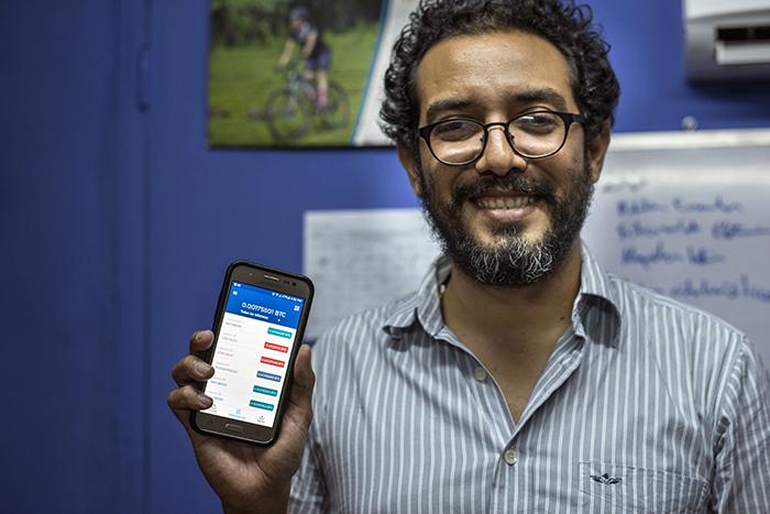 Denis Cáceres, fundador de Co-Labora, muestra su billetera electrónica, donde ahorra bitcoins.