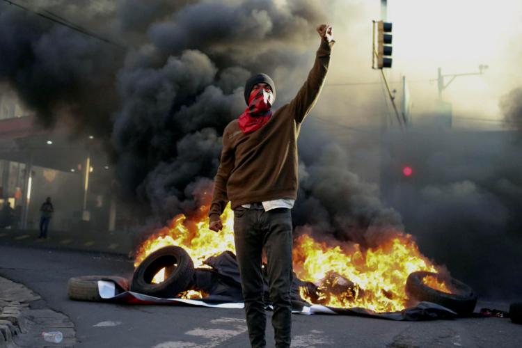 """Simpatizantes de la Alianza de Oposición contra la Dictadura queman llantas en la calle de acceso a la embajada en Tegucigalpa, para protestar contra el supuesto """"fraude electoral"""" en perjuicio de su candidato, Salvador Nasralla. LA PRENSA / EFE / Gustavo Amador"""