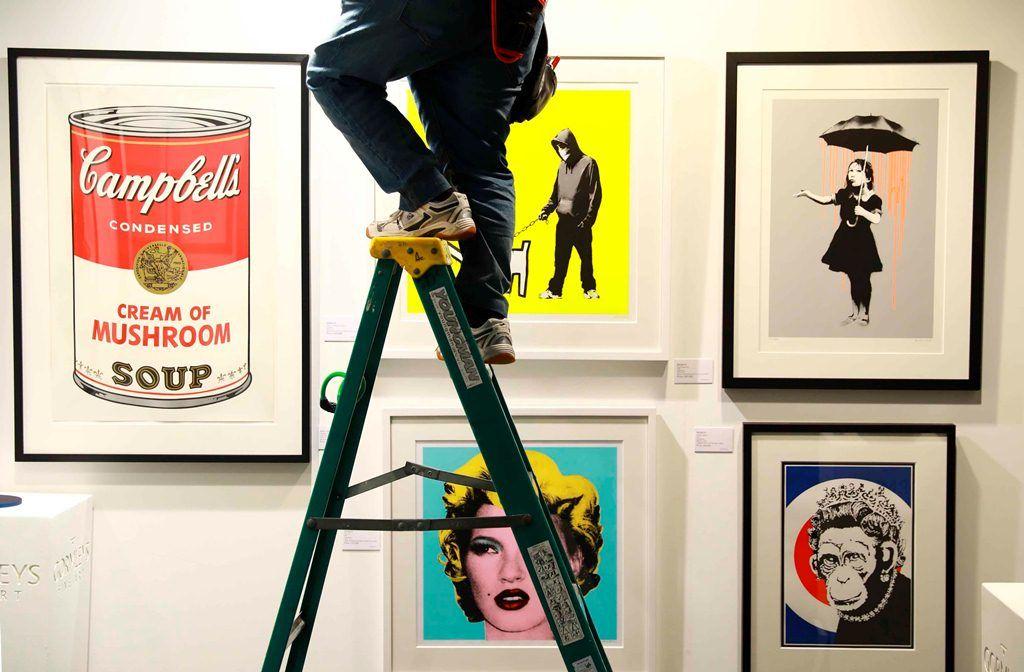 Un trabajador ajusta la iluminación de varias piezas de Andy Warhol y Bansky expuestas en al feria que conmemora su 30 aniversario. LAPRENSA/EFE/ Neil Hall