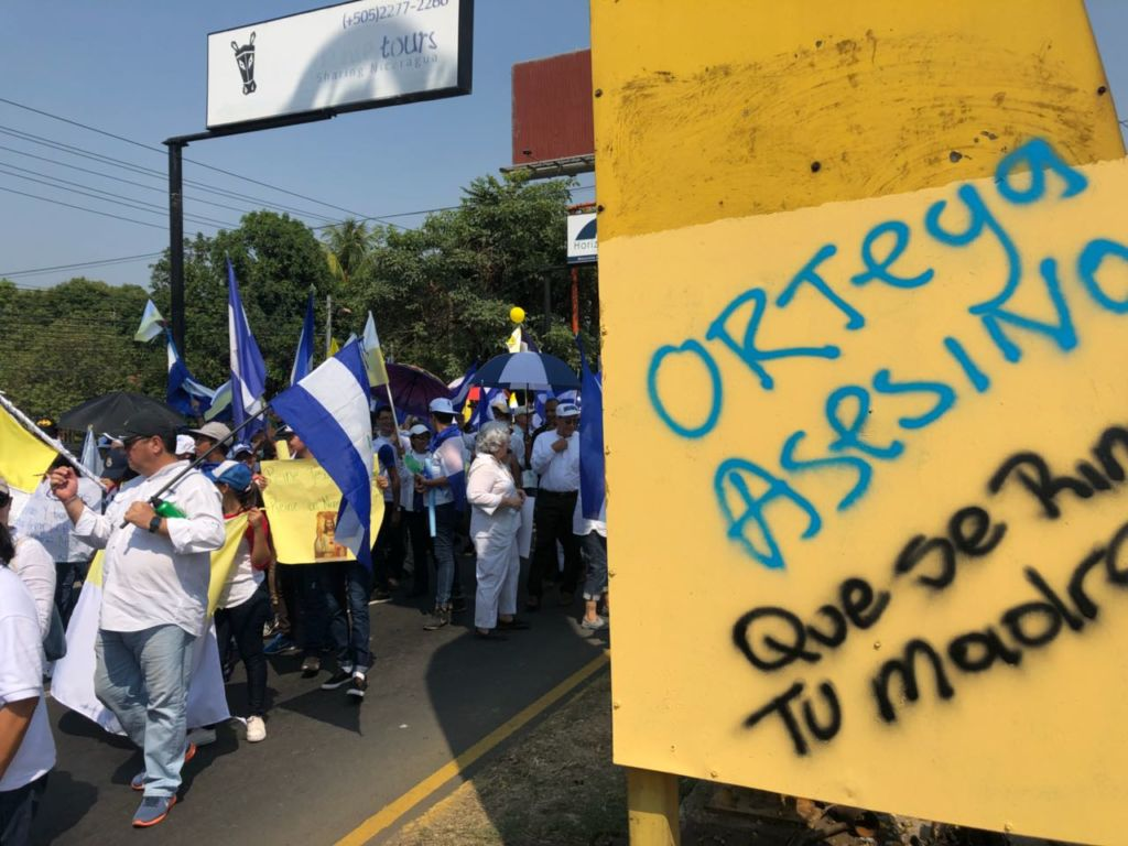 """La marcha al lado de los llamados árboles de la vida oficialistas. Aquí, al pie de uno de estos árboles conocidos popularmente como """"chayopalos"""", una pinta de otras protestas denuncia: """"Ortega asesino"""". LA PRENSA / Fabrice Le Lous"""
