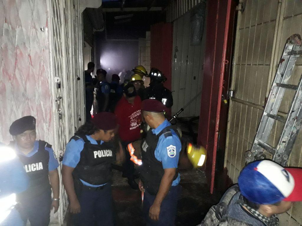 Bomberos y comerciantes continúan trabajando para controlar el incendio en el sector de los vaho en el mercado Oriental. LA PRENSA/ W. Narváez.