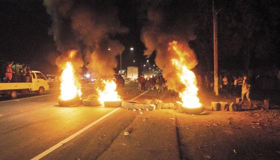 Estudiantes de la UNA y pobladores de barrios aledaños quemaban llantas anoche en Carretera Norte, después del ataque policial. La Prensa/Uriel Molina