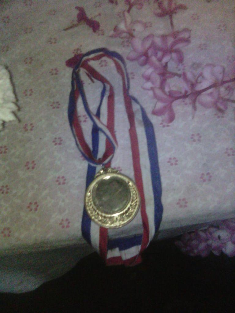 De acuerdo con la madre de Junior, el policía que le disparó a su hijo le había dado esta medalla en un torneo de futbol. LA PRENSA / Cortesía