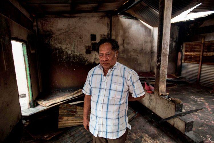 Wilfredo Suazo (de camisa a cuadros celeste), padre de Yubrank Suazo, dirigente del Movimiento 19 de Abril, observa lo que quedó de su casa, en Masaya, la cual fue incendiada por hordas del Gobierno. LA PRENSA/ AFP
