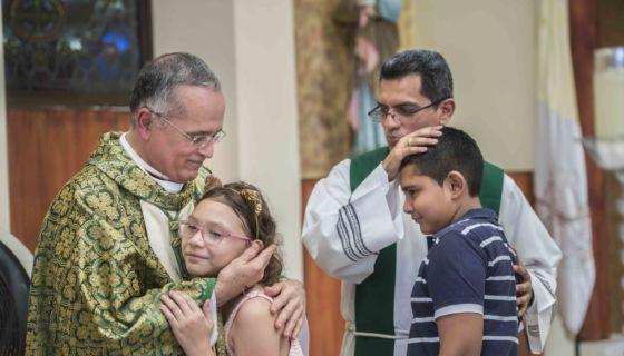 Monseñor Silvio Báez, abraza a los niós luego de finalizar homilía en parroquia San Miguel Arcángel